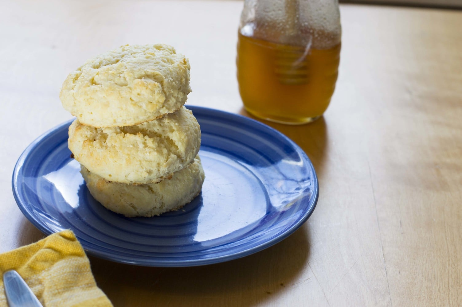 Fresh biscuits on a plate with honey in the background
