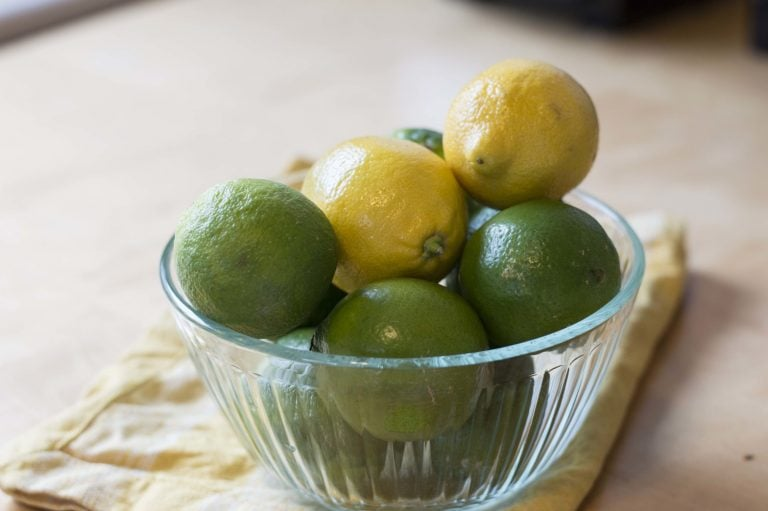 Glass bowl filled with lemons and limes