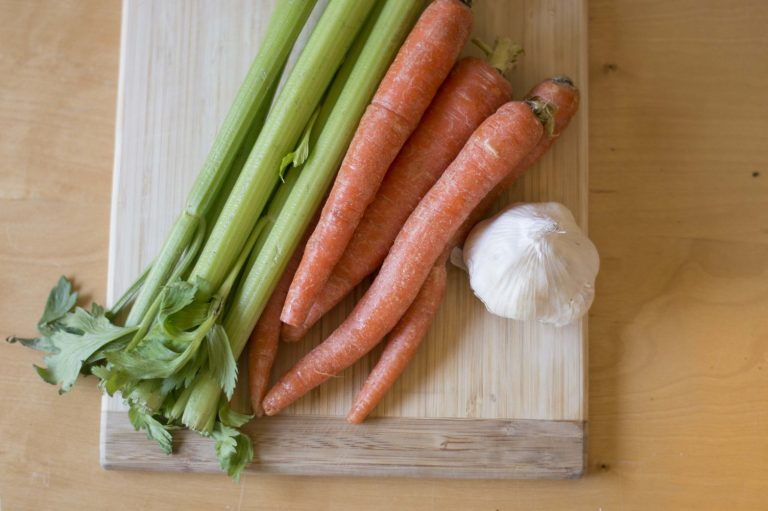 Carrots, celery and garlic on a wood cutting board