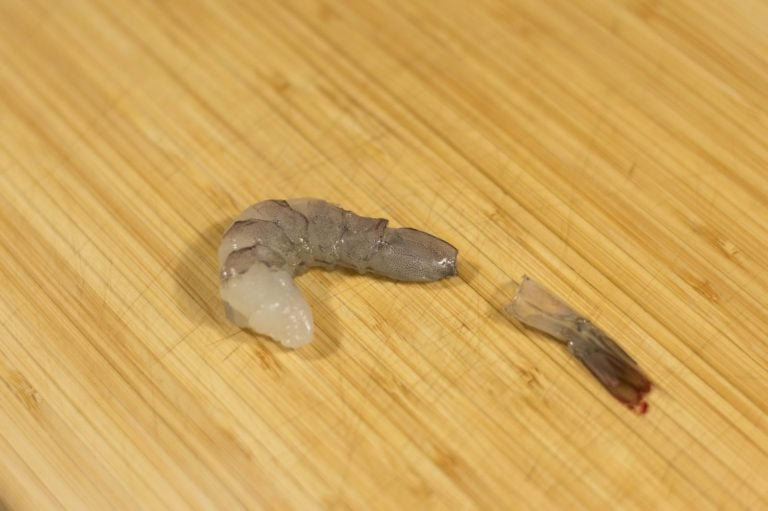 Demonstrating how to peel a perfectly cooked shrimp