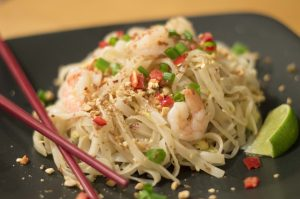 close up pad thai with shrimp all dished up with a lime garnish