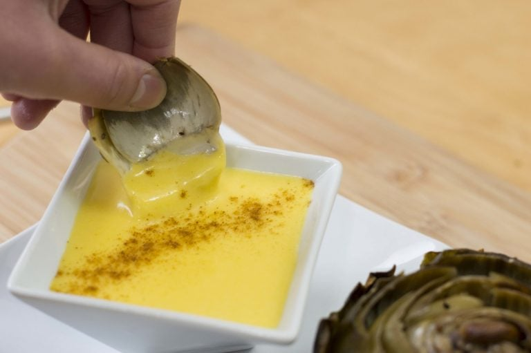 Dipping a baked artichoke leaf into the hollandaise sauce