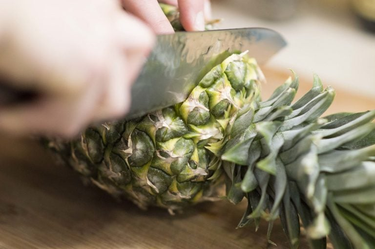 Removing the pineapple crown to show you how to cut a pineapple