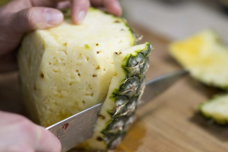 Removing more of the sides to show you how to cut a pineapple