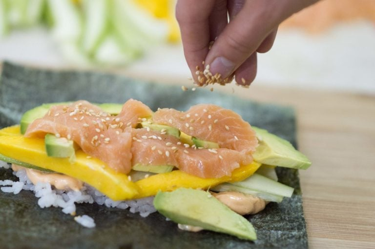 Adding toasted sesame seeds to the Salmon Sushi Wrap