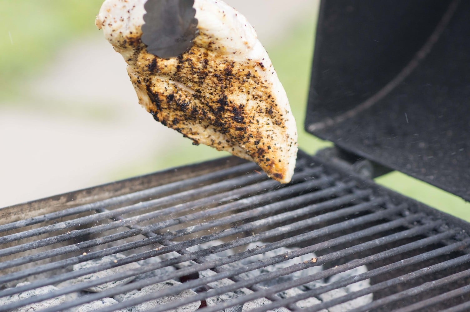Flipping chicken on the grill for the Marinades & Brining tutorial