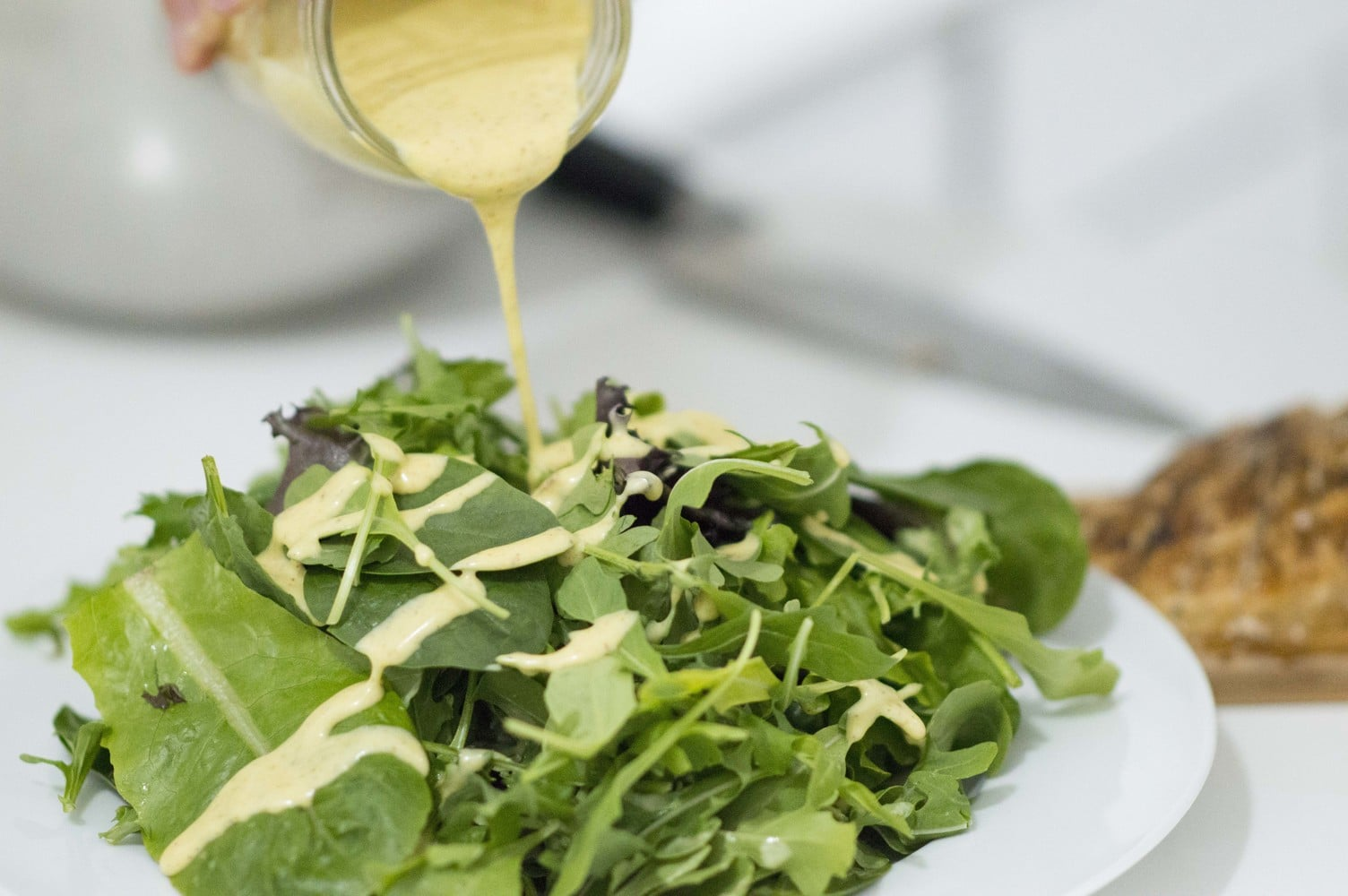 Tangy Honey Mustard Sauce being poured over a salad