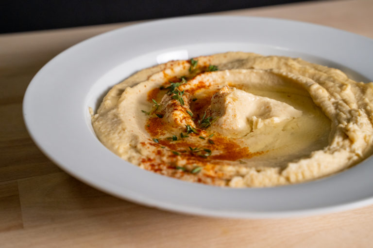 a bowl of hummus with paprika, herbs, and oil