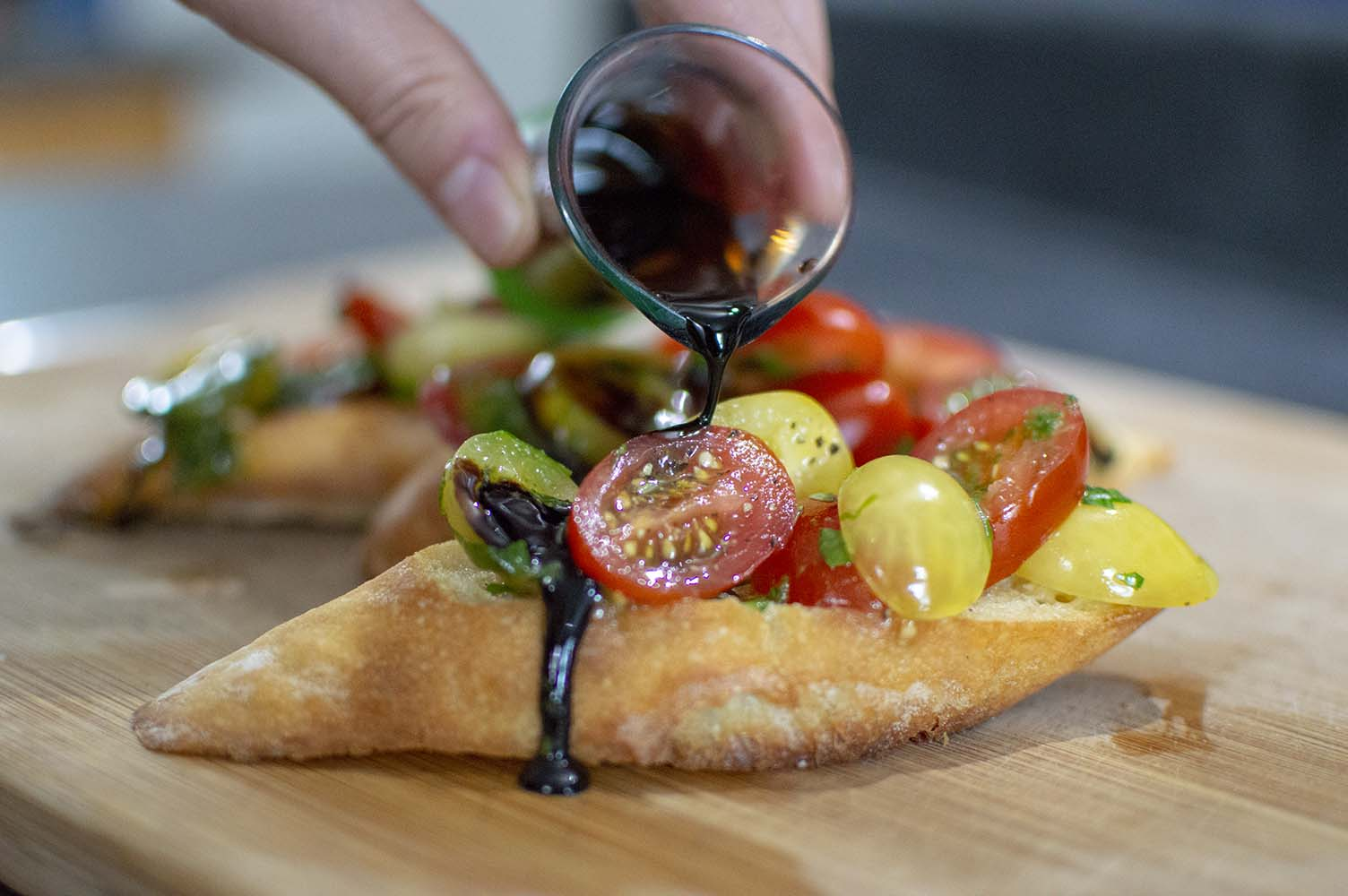 Topping the Tomato Brushetta with balsamic reduction