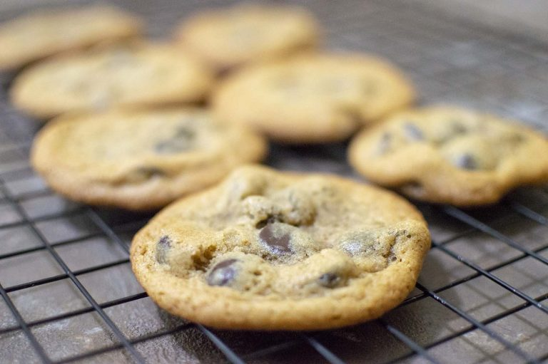 Chewy chocolate chips cookies on a screen cooling