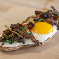 A fancy toast with goat cheese, mushrooms, and a sunny-side egg.
