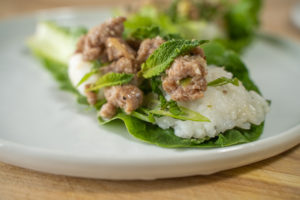 Larb salad with sticky rice in a lettuce cup