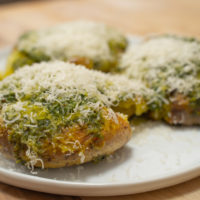 Roasted potatoes on a plate with a green sauce and cheese