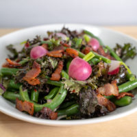 a bowl of salad with green beans, radishes, kale, and bacon
