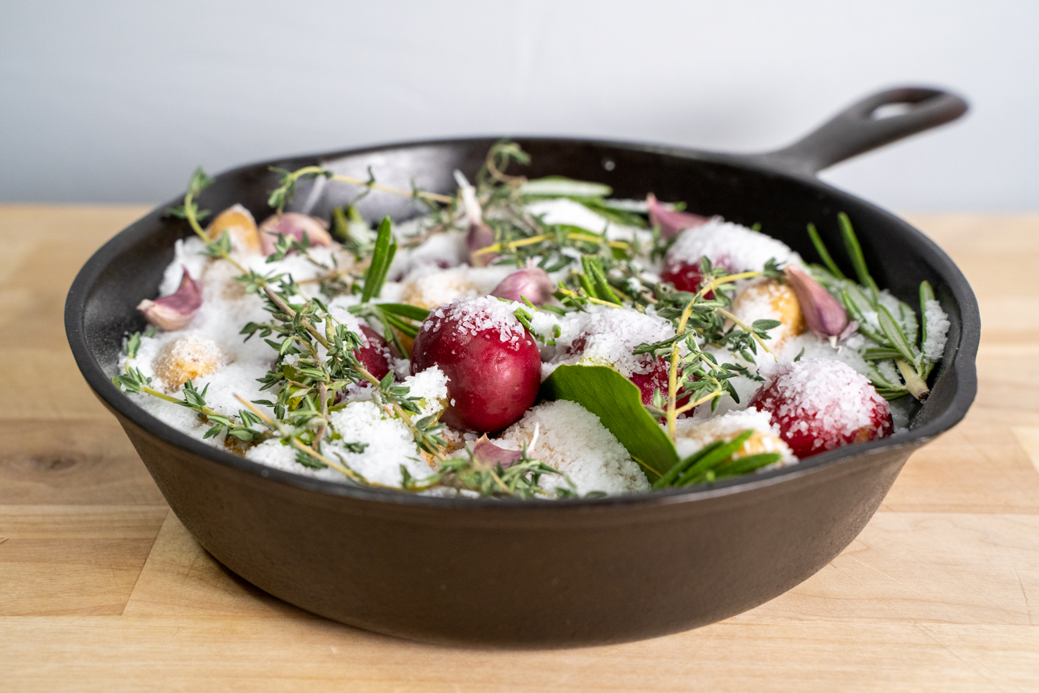 Cast iron pan of salt roasted potatoes with herbs