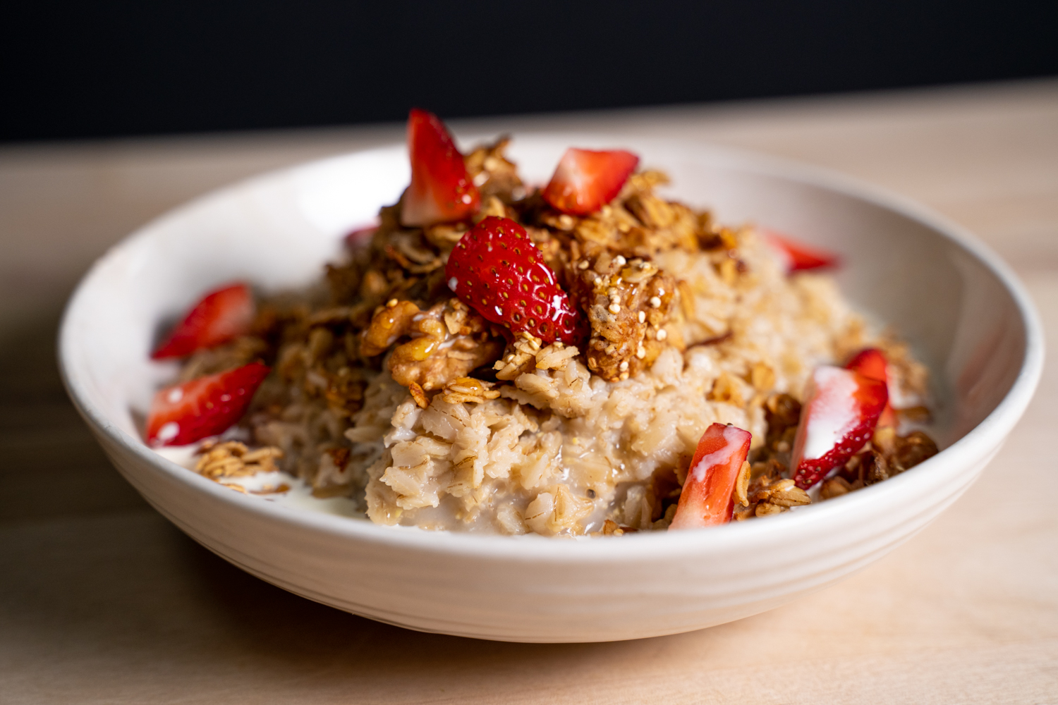 A bowl of oatmeal with honey dripping down over strawberries and granola