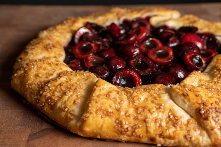 A browned crust with sugar crystals and shiny cherries.
