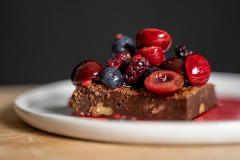 brownies on a plate with syrupy berries piled on top
