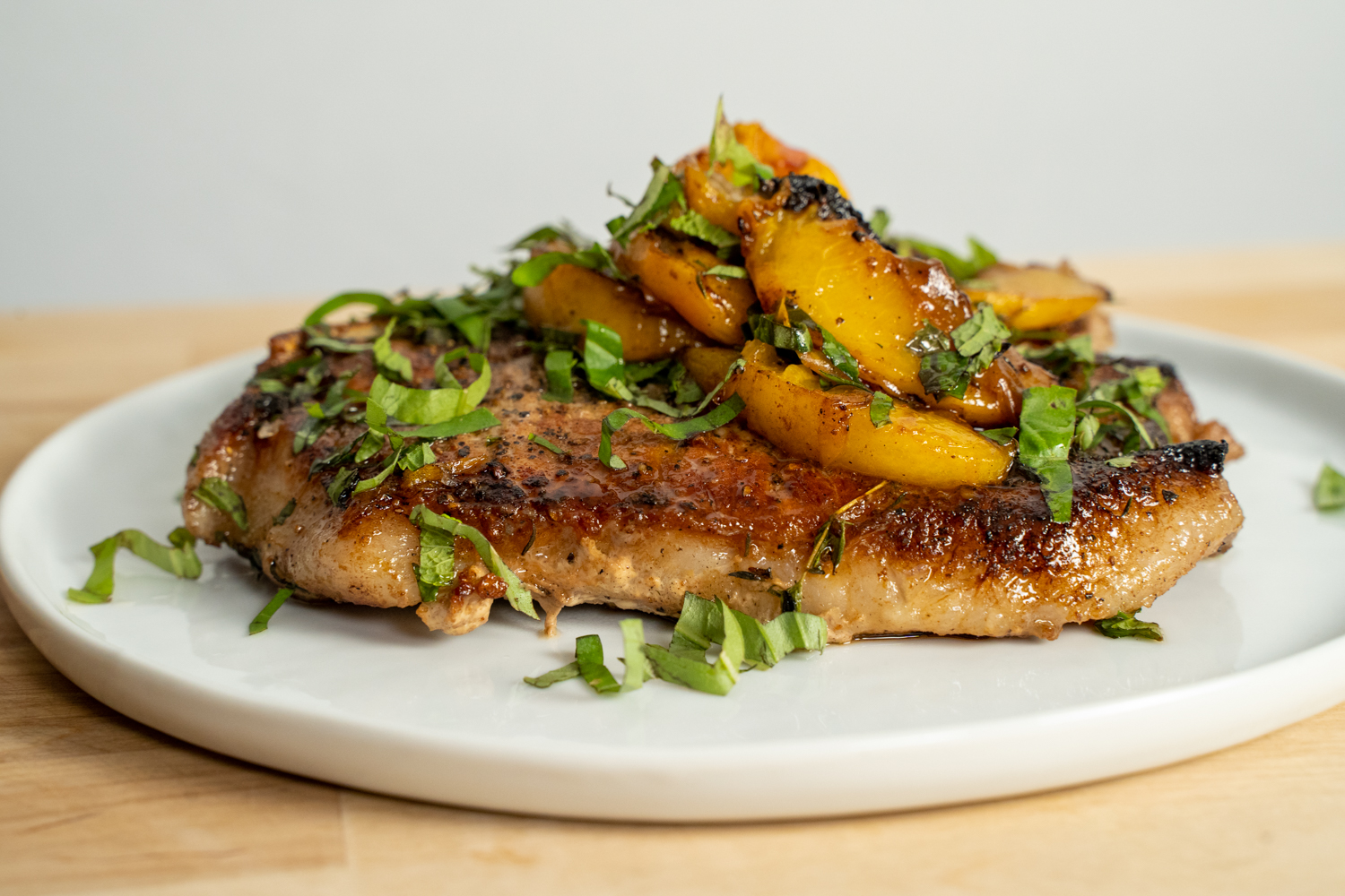 seared pork chop on a plate topped with peaches and herbs